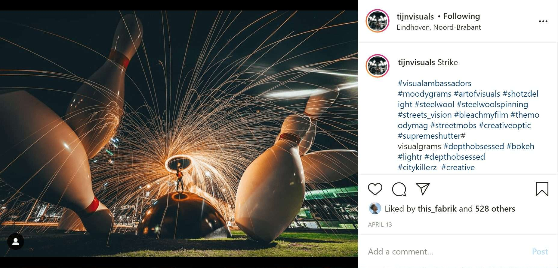 taken at night, a man stands on top of a bowling ball monument moving a sparkler above his head to create a circle of light around him