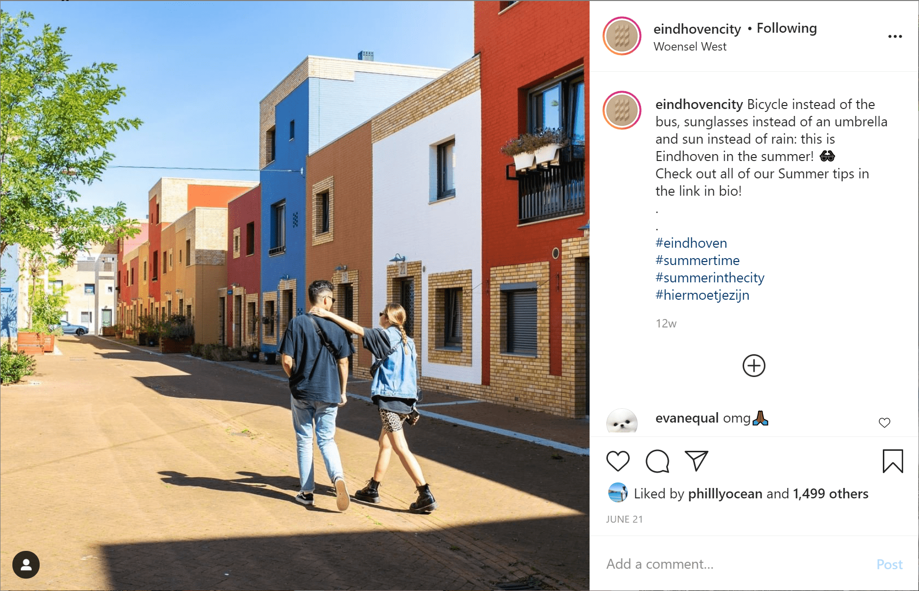 a man and woman wearing blue denim walk in front of colourful houses in Eindhoven