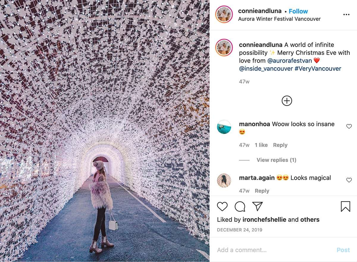 lady standing in a tunnel of pale pink lights at the Aurora Winter Festival Vancouver
