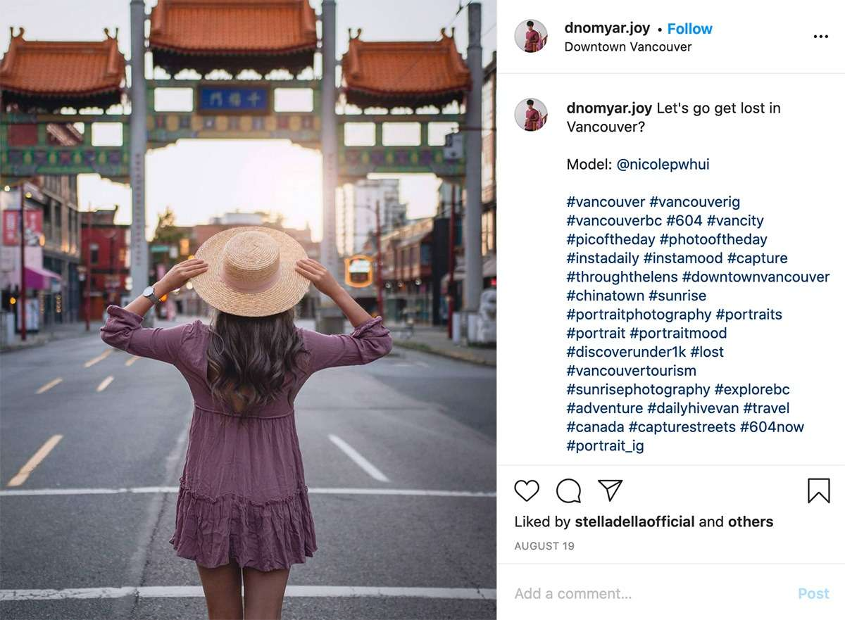 woman in purple dress and straw hat stands in front of Chinatown Millennium Gates in Vancouver