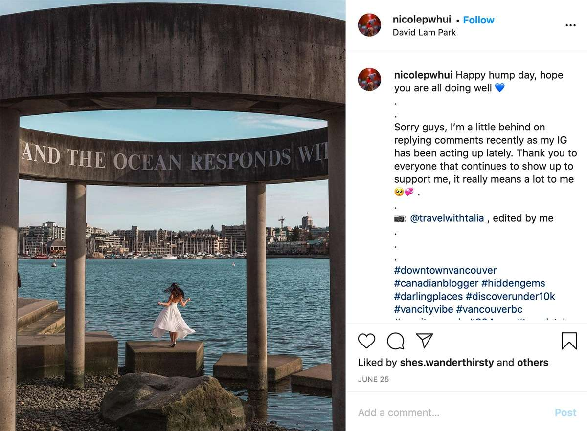 lady in white dress poses on the waterfront at David Lam Park in Vancouver