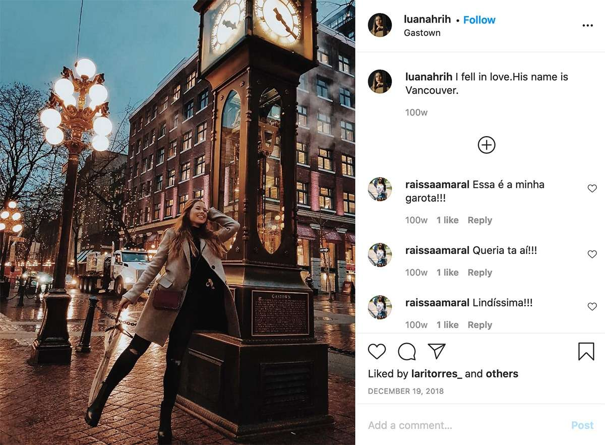 lady wearing a brown coat poses beside the Gastown Clock in Vancouver