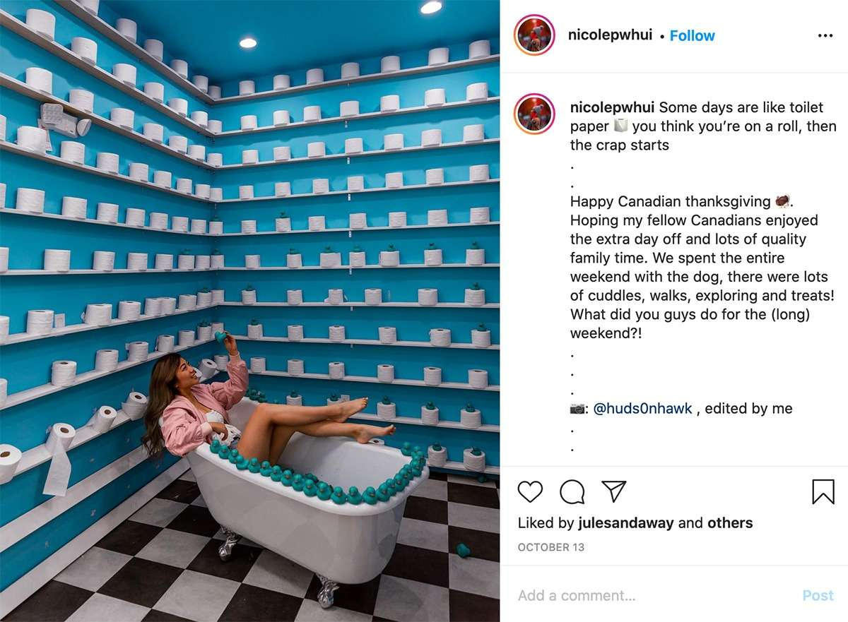 lady poses in a bathtub in a room filled with rolls of toilet paper at Pretty Lucid Place, one of the most Instagrammable places in Vancouver