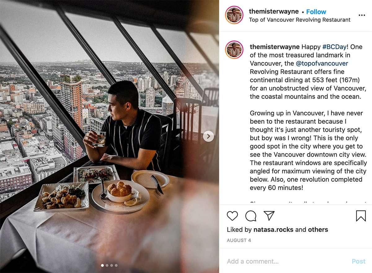 man eating a meal at Top of Vancouver Revolving Restaurant with a view down over the city