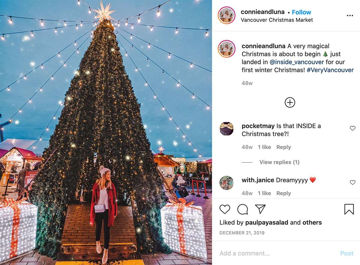 lady poses by a large Christmas tree as the Christmas Markets at Canada Place in Vancouver