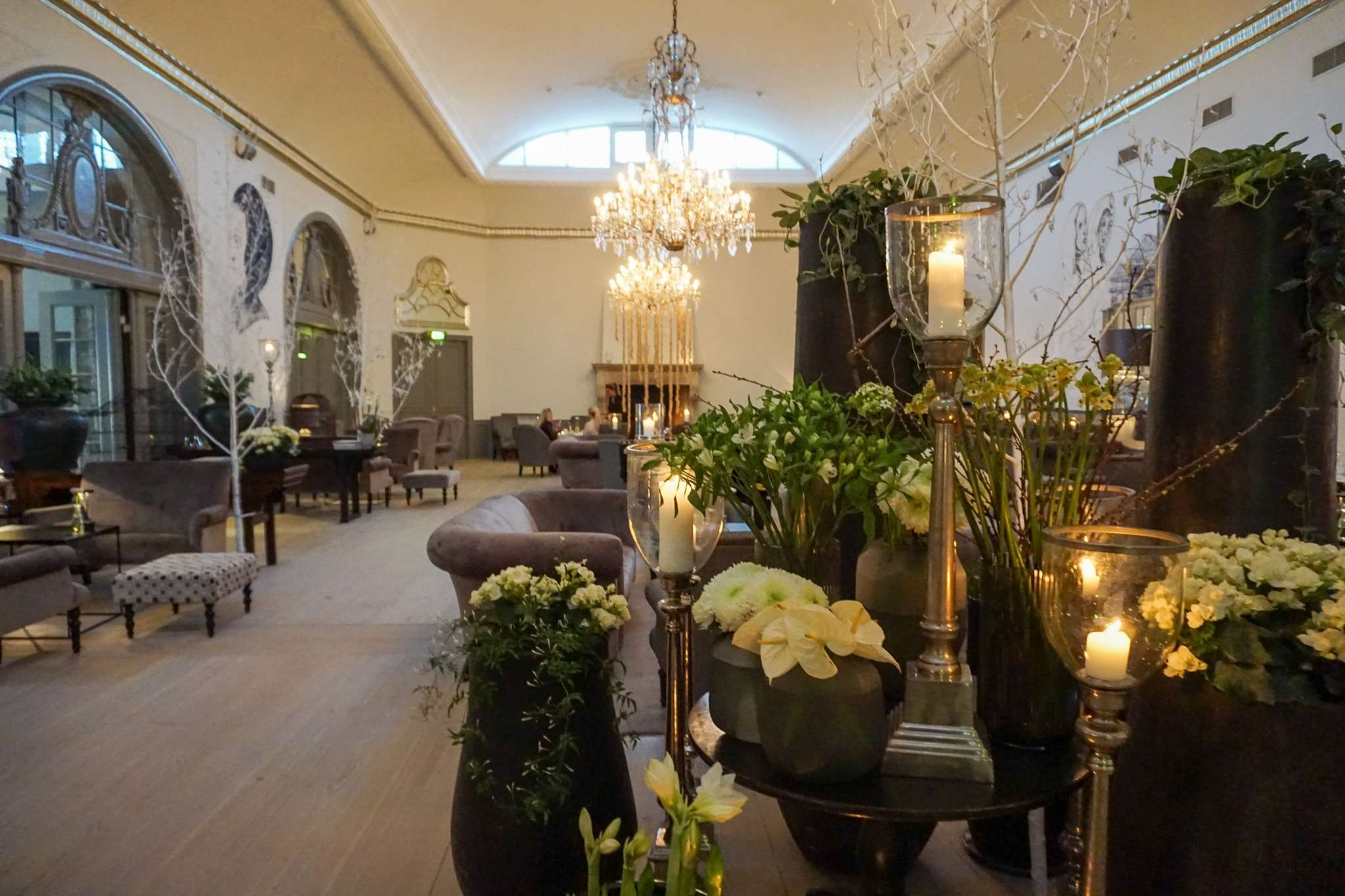 Large hall in Nimb Hotel Copenhagen decorated with flowers and a large chandelier