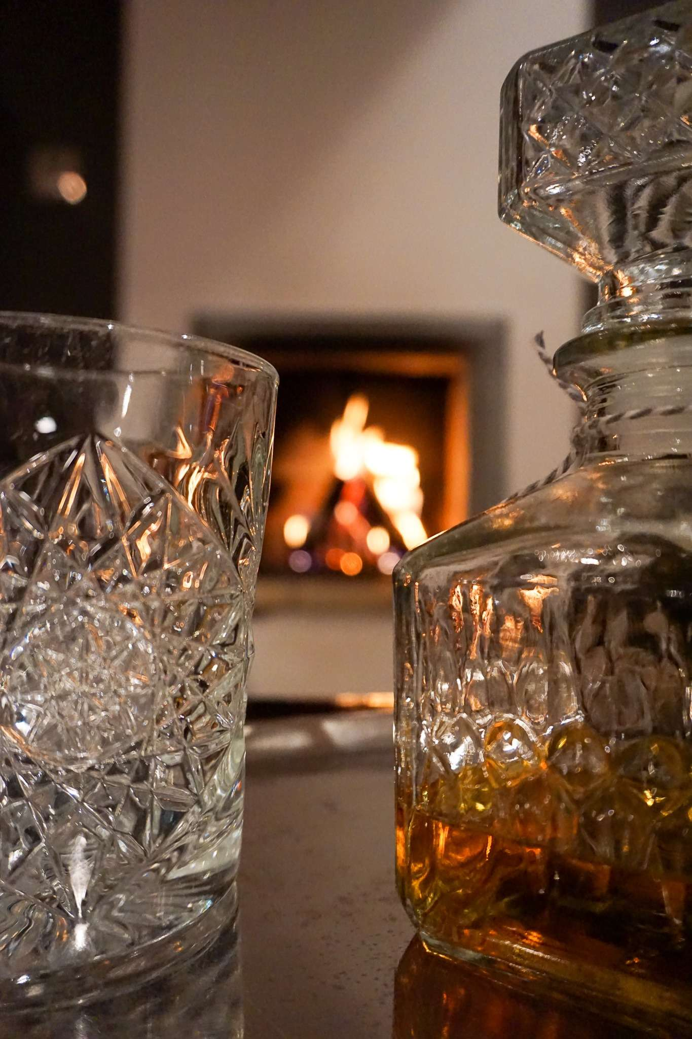 whiskey glass and decanter in front of a lit fireplace at Nimb Hotel Copenhagen