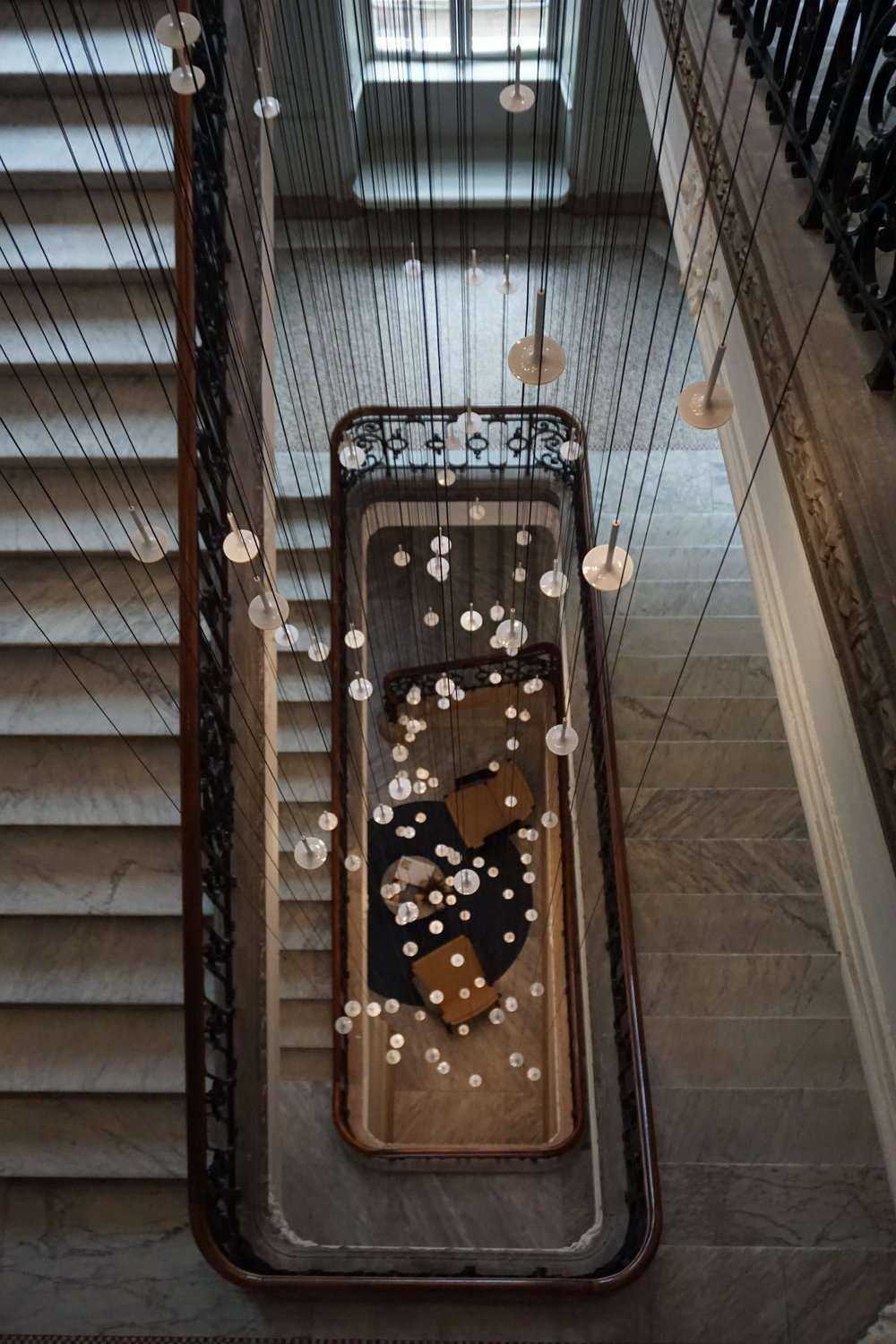 looking down the spiral staircase with decorative hanging lights at Nobis Hotel Copenhagen