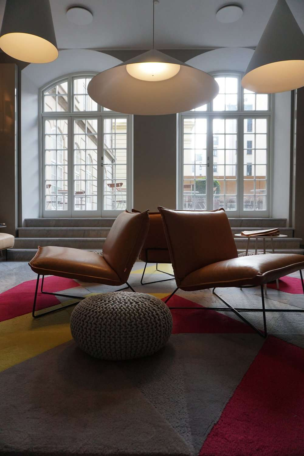 contemporary brown leather chairs and a brightly coloured carpet in the entrance to Nobis Hotel Copenhagen