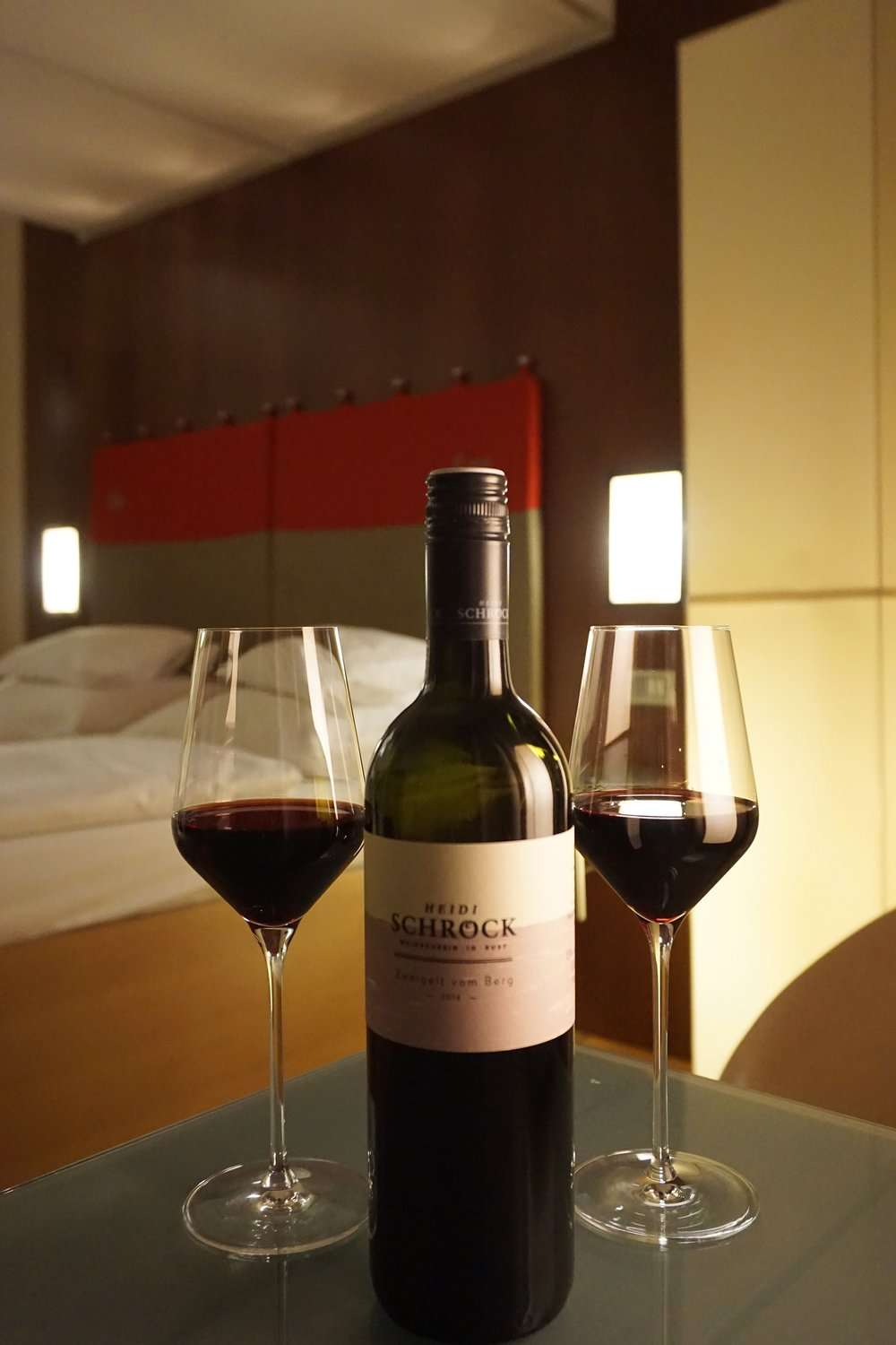 bottle and 2 glasses of red wine in the bedroom at Rathaus Wein & Design Hotel Vienna