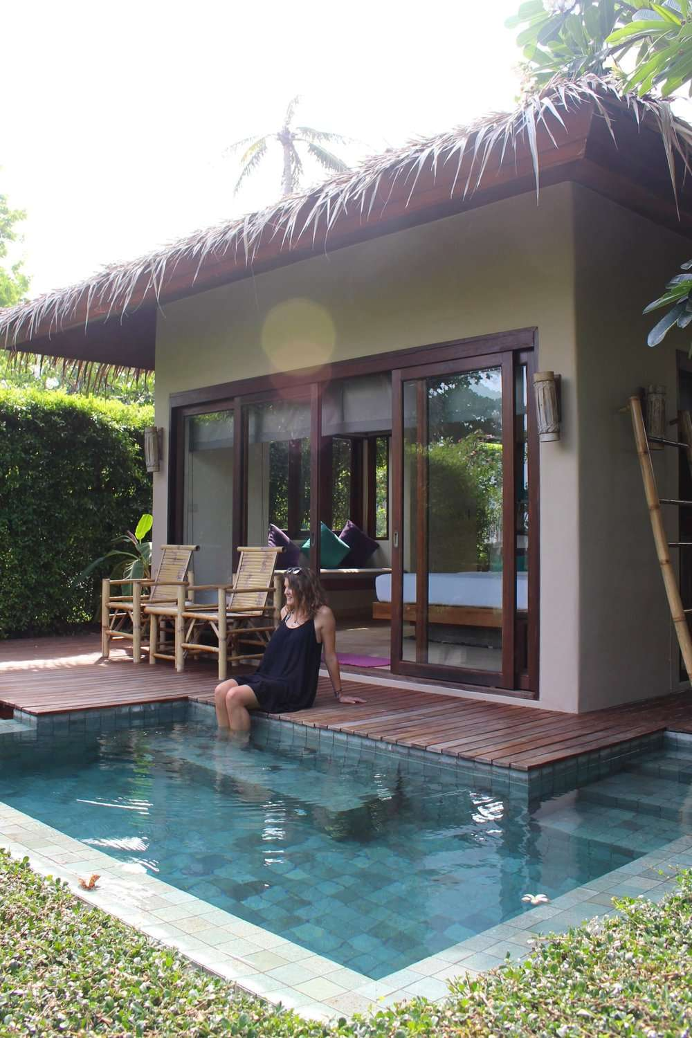 lady wearing a black dress sits at the edge of a pool beside a cabana in Sea Dance Resort Koh Samui