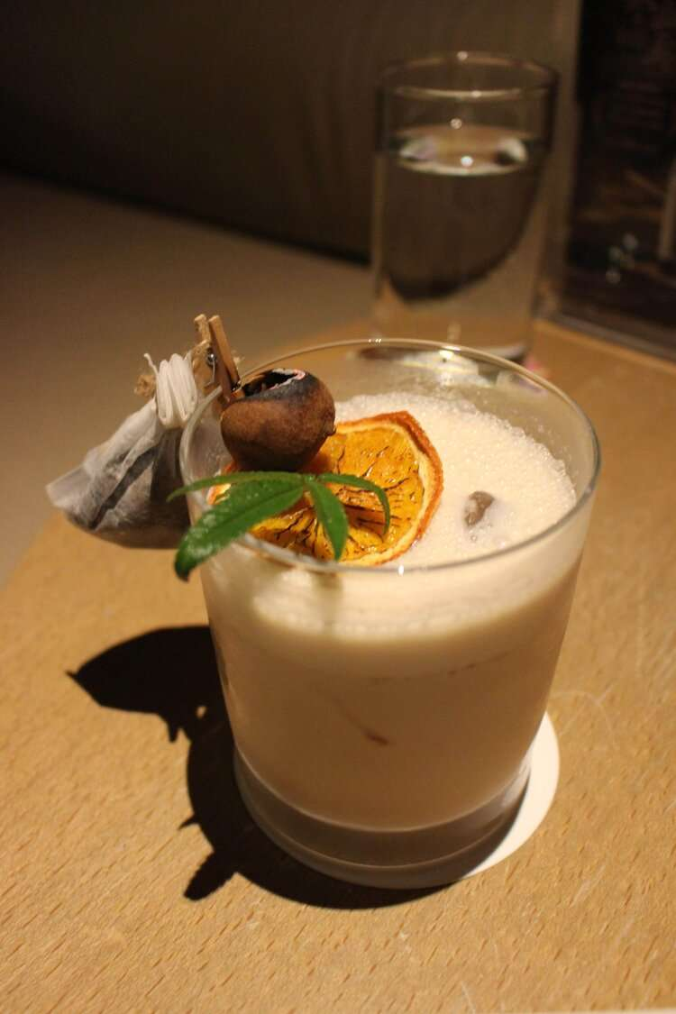 creamy signature cocktail with decorative spices and orange ring, at Silks Place Tainan