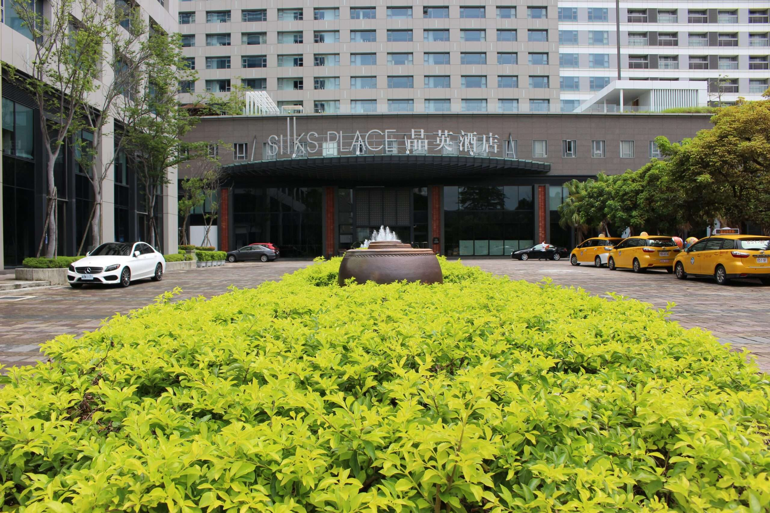 Long green bush leads to the entrance of Silks Place hotel in Tainan