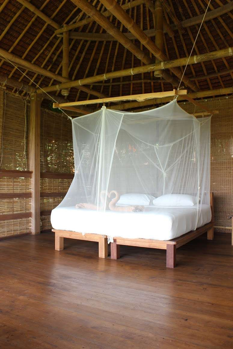 large bed with mosquito net cover in the treehouse at The Island Hideout Koh Yao Noi