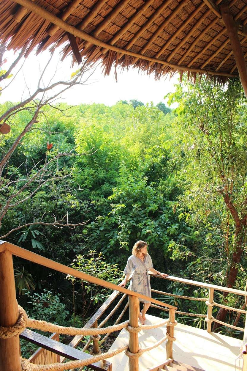 lady stands at the fence of the treehouse overlooking the lush jungle at The Island Hideout Koh Yao Noi