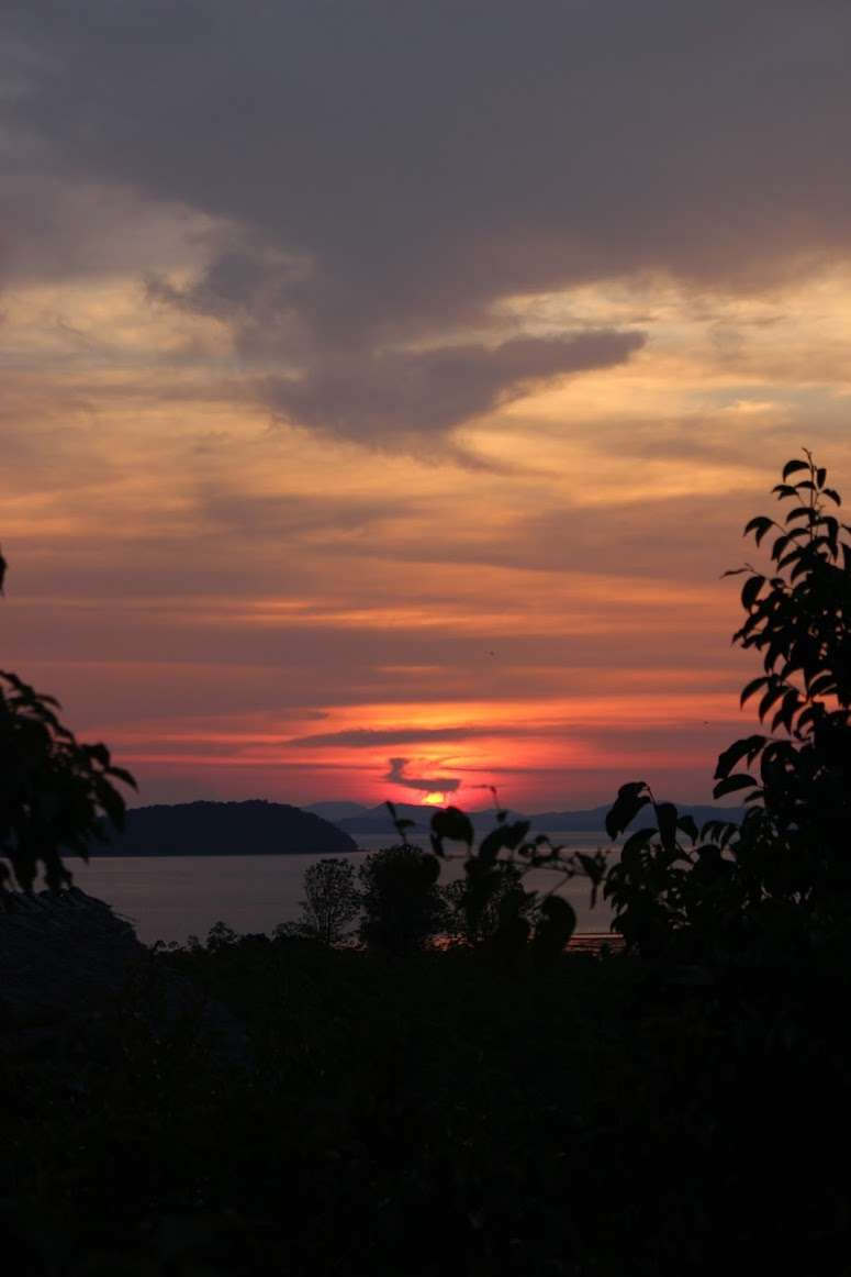 dark pink and orange sunset sky over the trees, sea and islands in the distance at The Island Hideout Koh Yao Noi