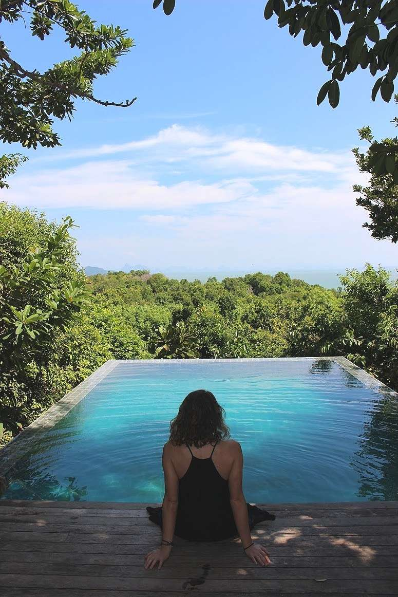 lady in a black dress sits at the edge of a swimming pool overlooking the treetops at The Island Hideout Koh Yao Noi