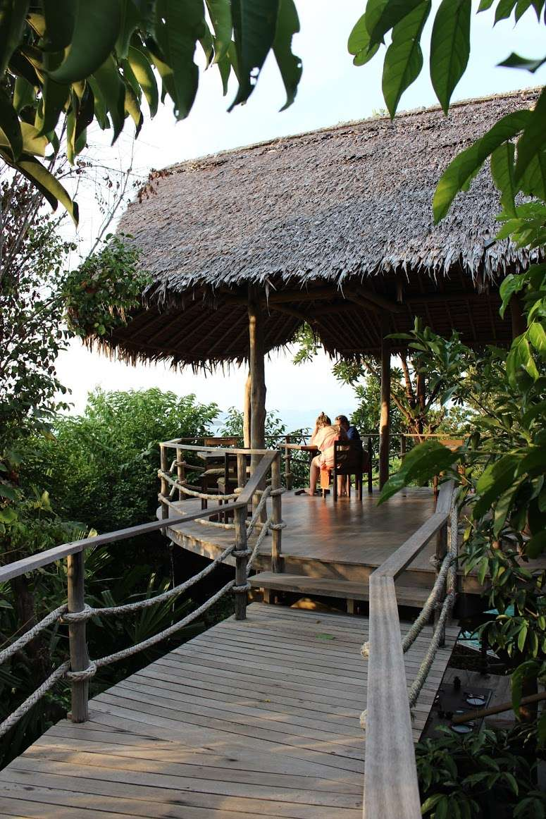 wooden bridge leads to a covered dining area at The Island Hideout Koh Yao Noi