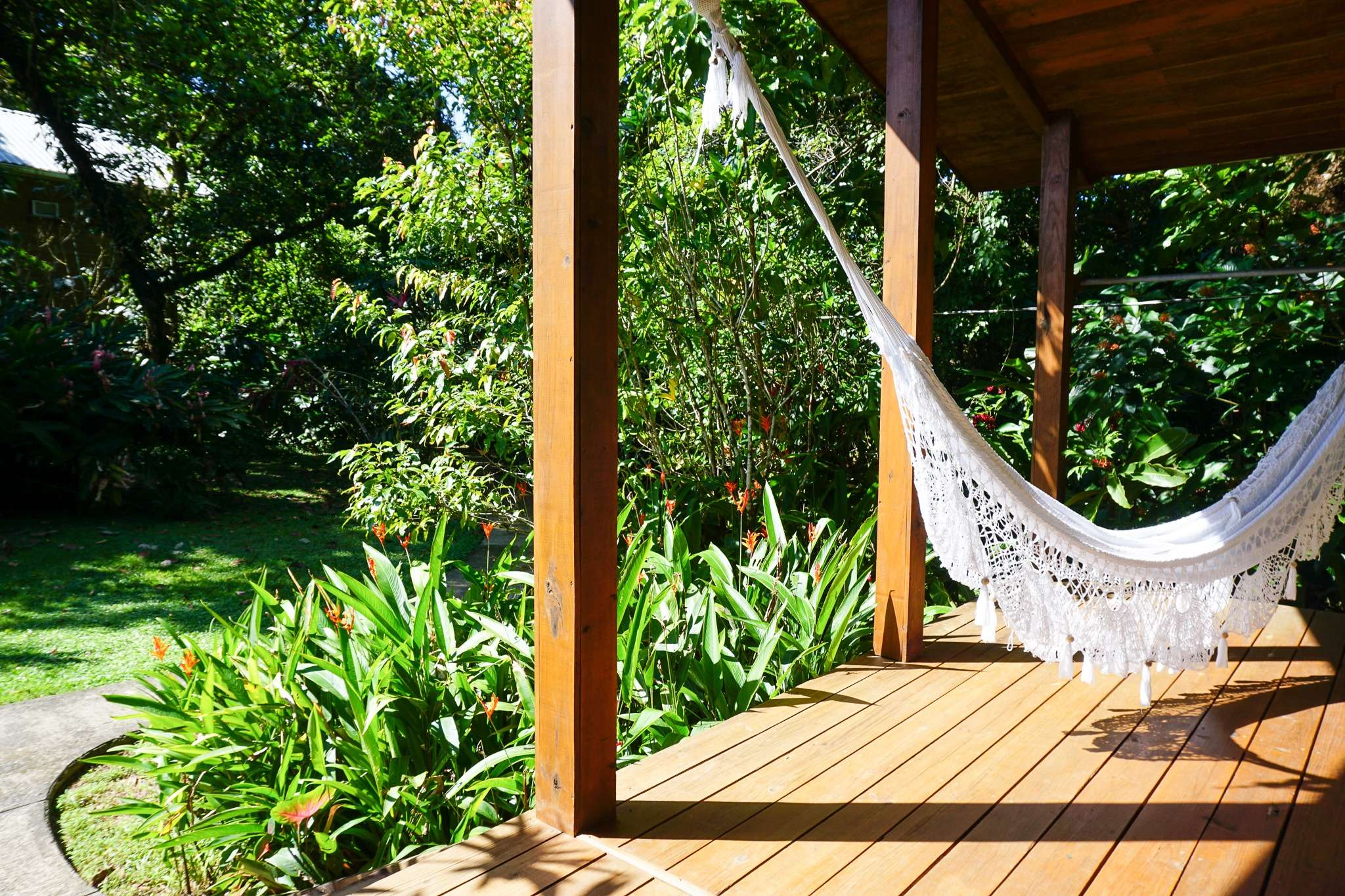 white hammock hangs on the veranda of a cabana at Tranquilo Bay, surrounded by tropical plants