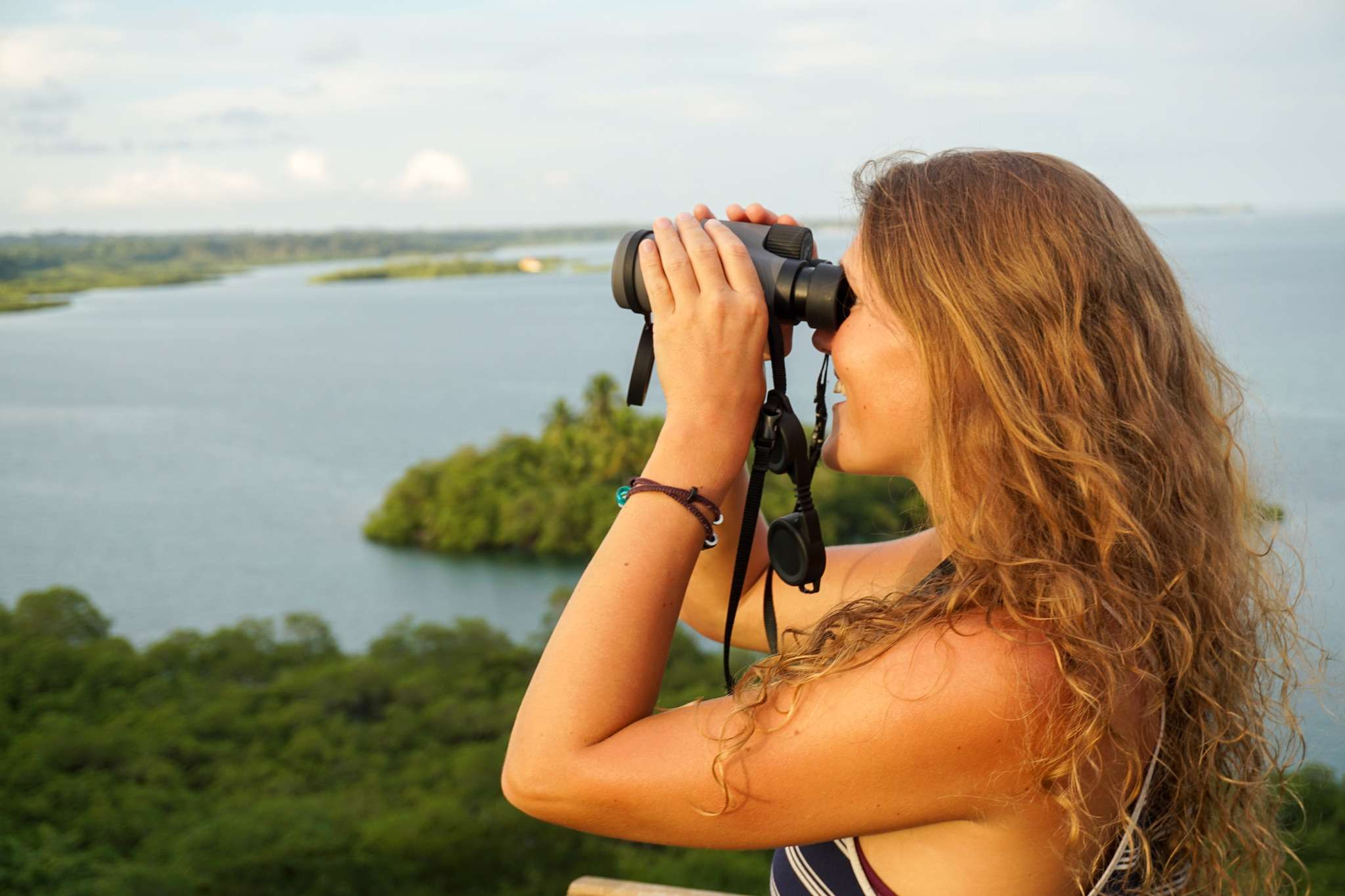 lady with long curly hair looks through binoculars with the sea and trees in the background at Tranquilo Bay Panama