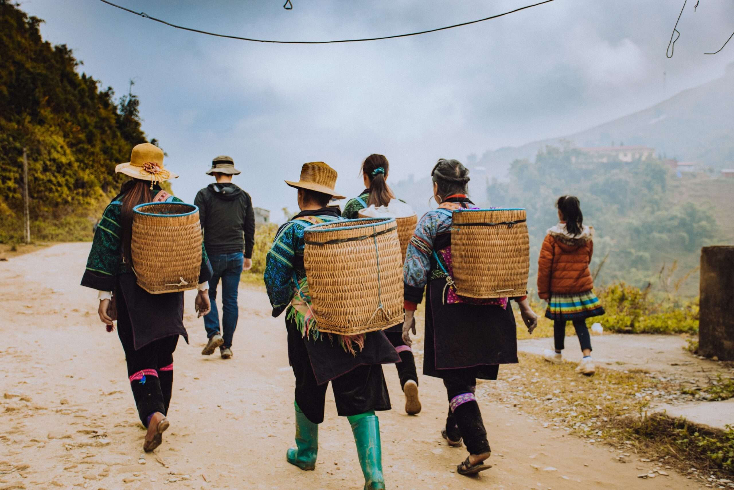 group of people carry woven baskets on the backs as they go trekking in Sapa