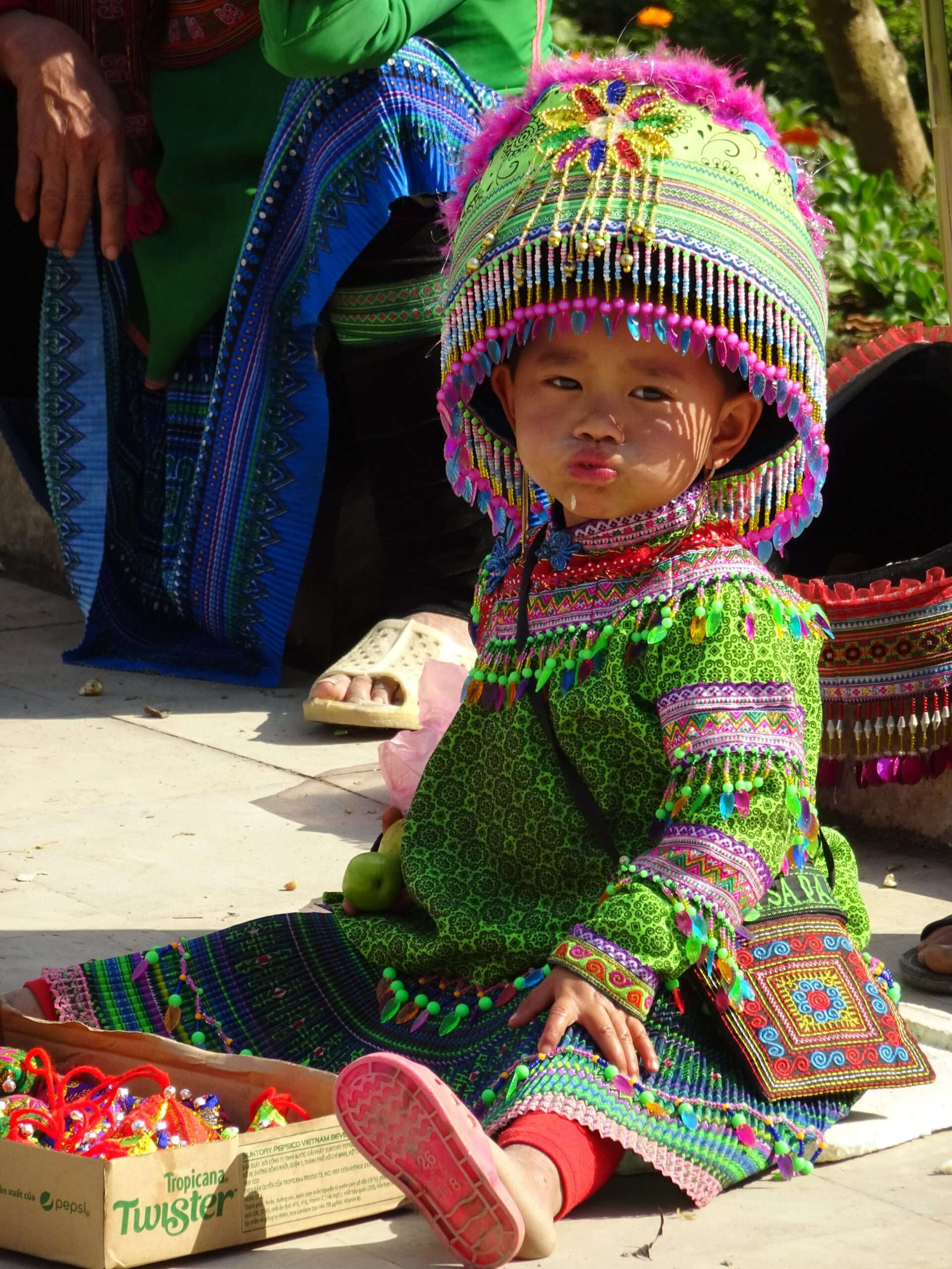 toddler wearing bright green and pink traditional dress, seen whilst trekking in Sapa Vietnam