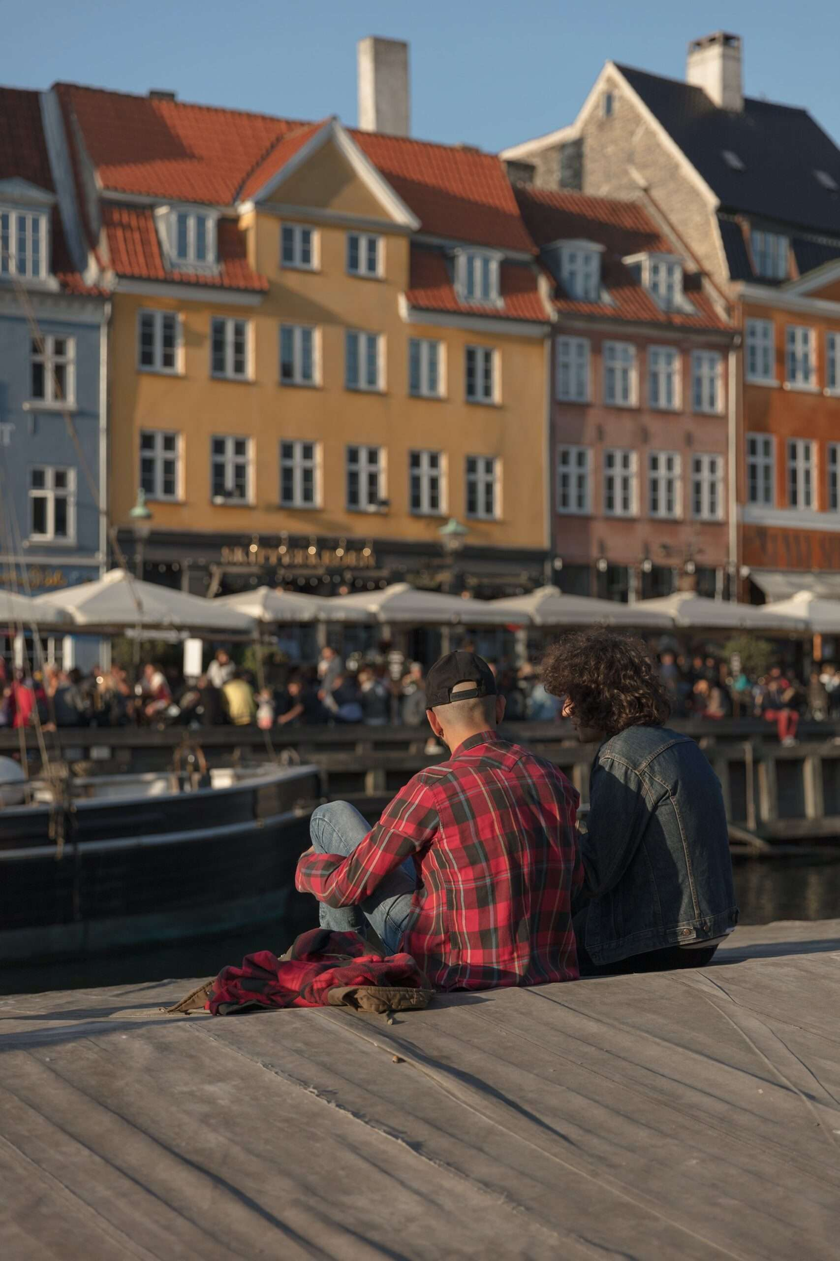 a couple sit on the waters edge at Nyhavn in Copenhagen, one of the best things to do in Copenhagen