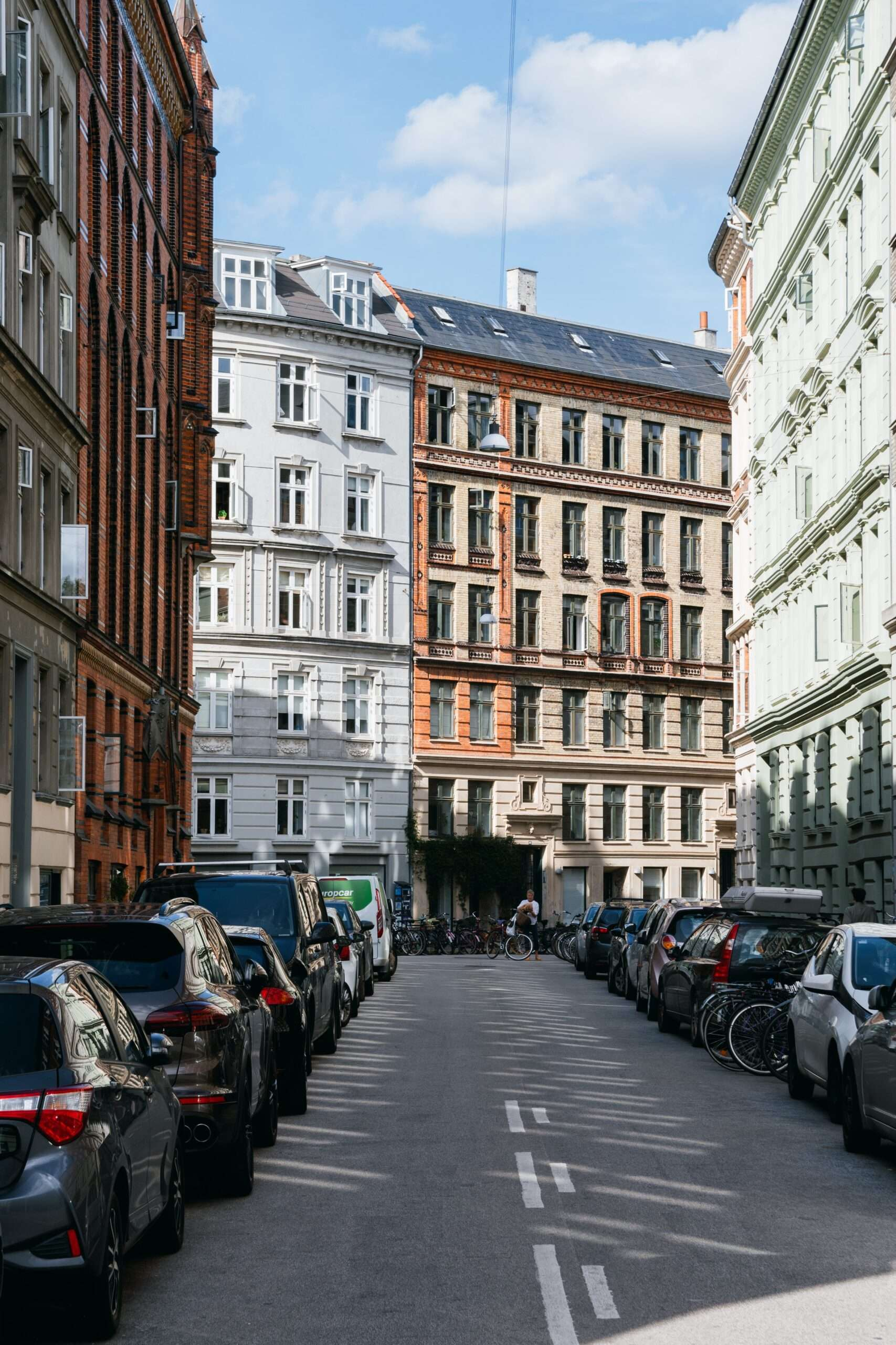 a street in Copenhagen with 6 storey buildings in brown brick andwhite paint