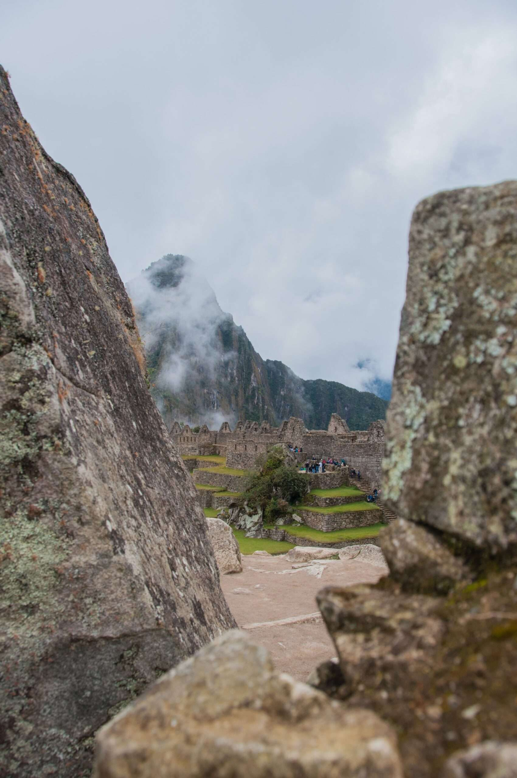 looking through a gap between large rocks onto the ruins of Machu Picchu at the end of the Salkantay Trek