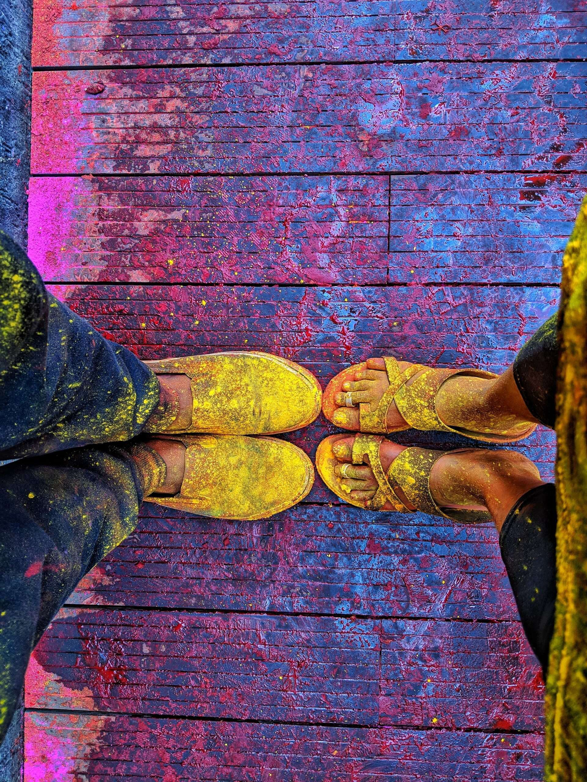 Two peoples clothing and feet covered in yellow powder at Holi festival