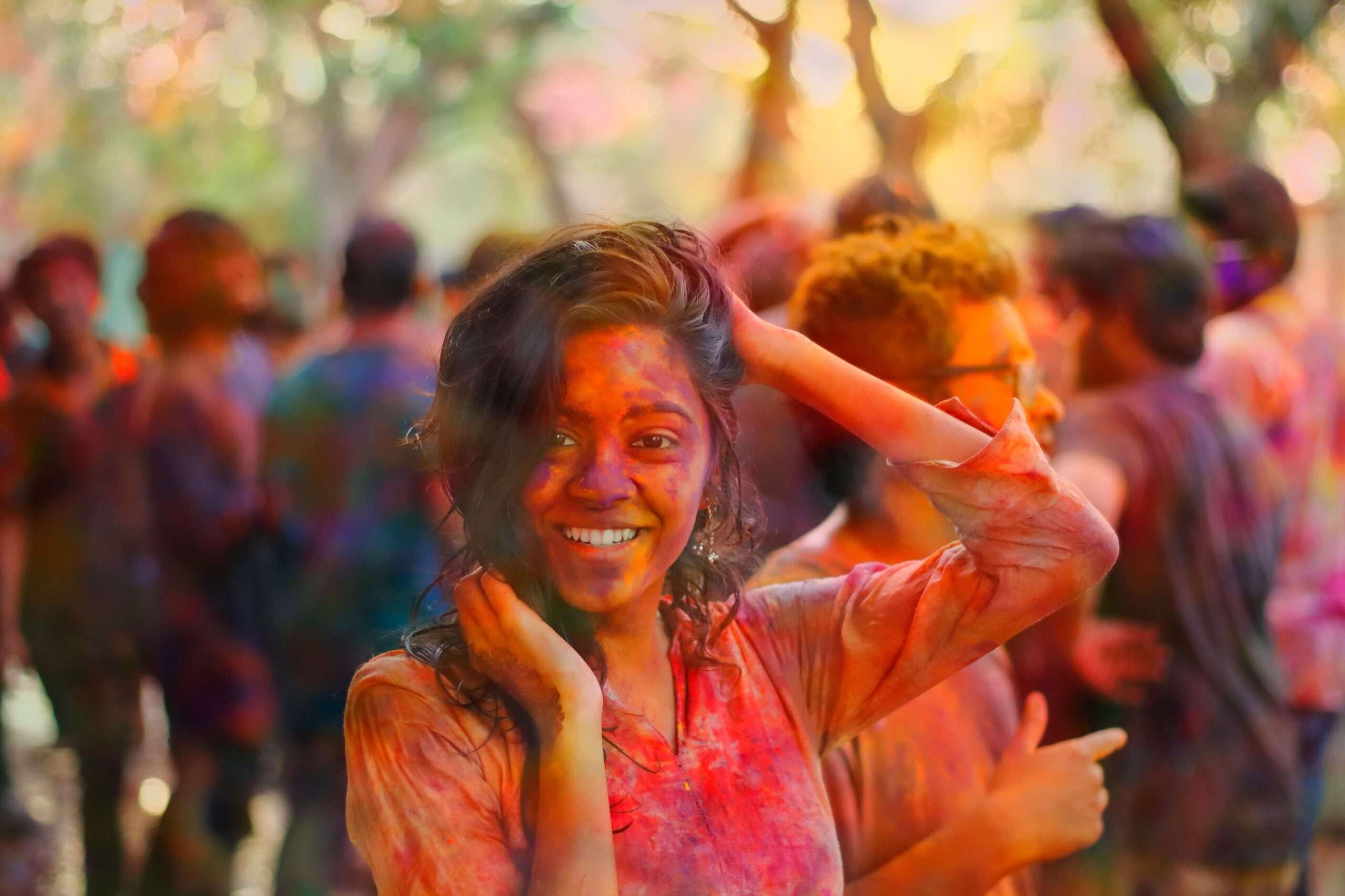 Girl covered in colourful powder smiles during celebration of Holi festival