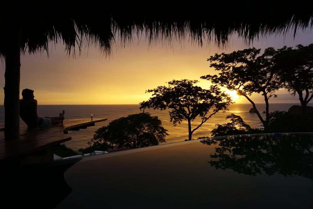Man watches the sun set at Hush Maderas