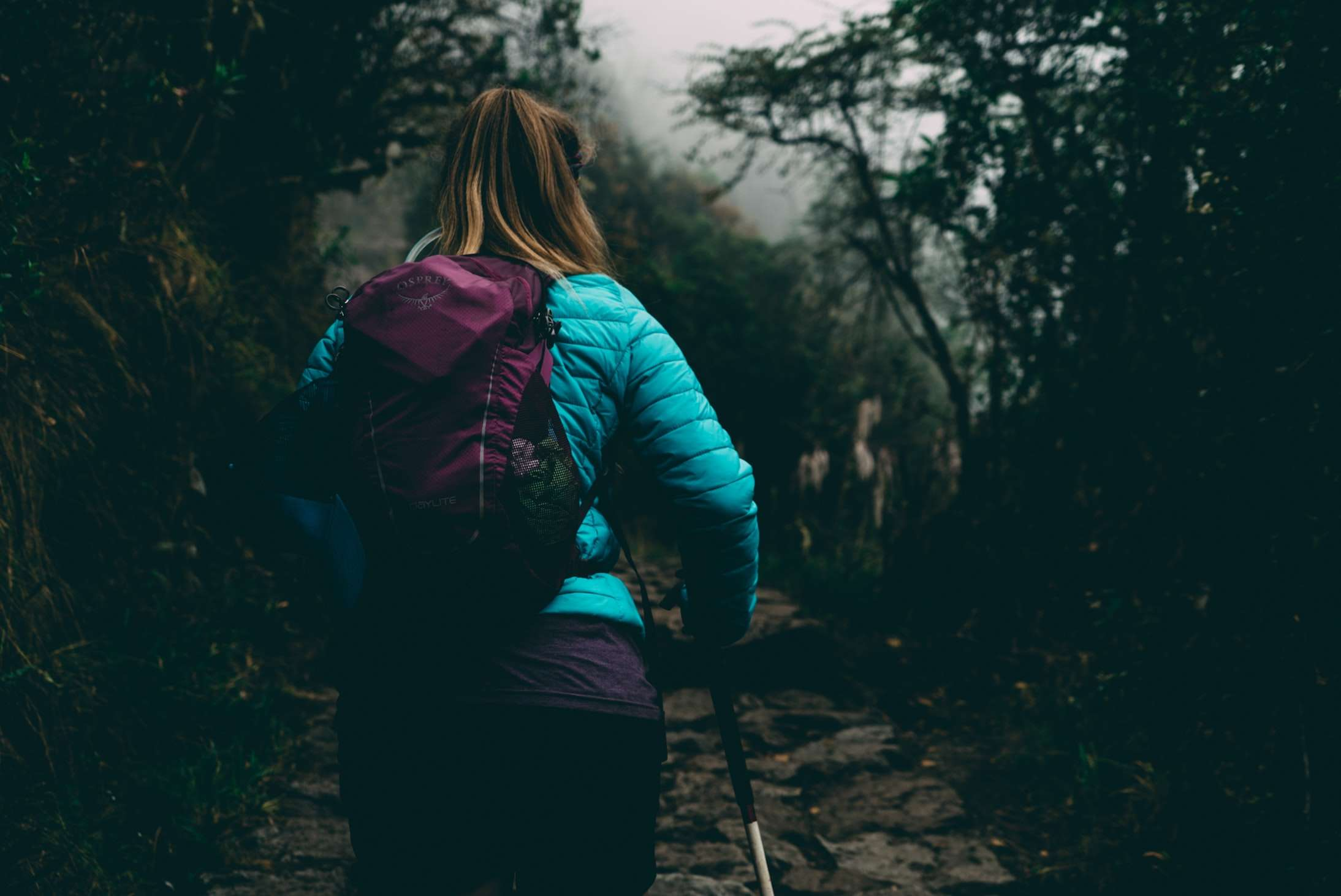 a lady wearing a turquoise coat and purple backpack hikes the Salkantay Trek