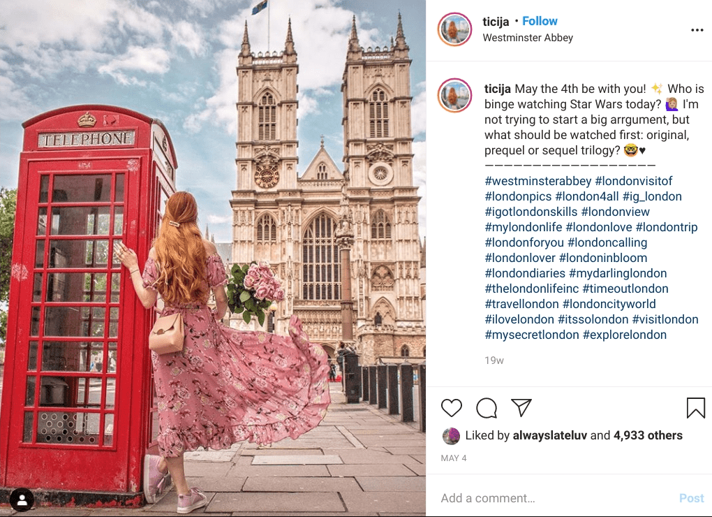 Woman stands next to phone booth in front of Westminster Abbey. One of Lost Tribe's most instagrammable places in London.