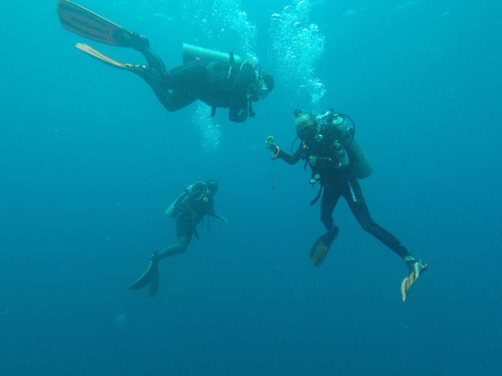 Scuba divers counting down before safely returning to the surface