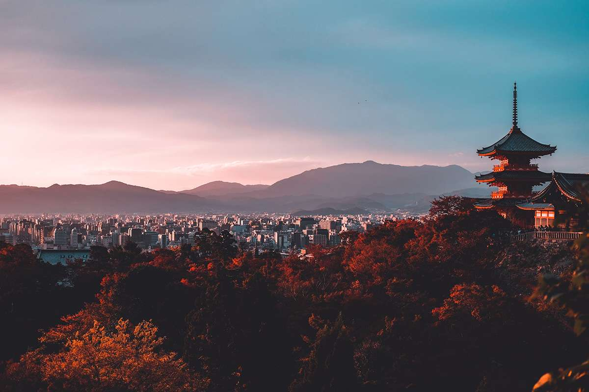 Kyoto at sunrise, seen from the mountain, with a temple in the foreground
