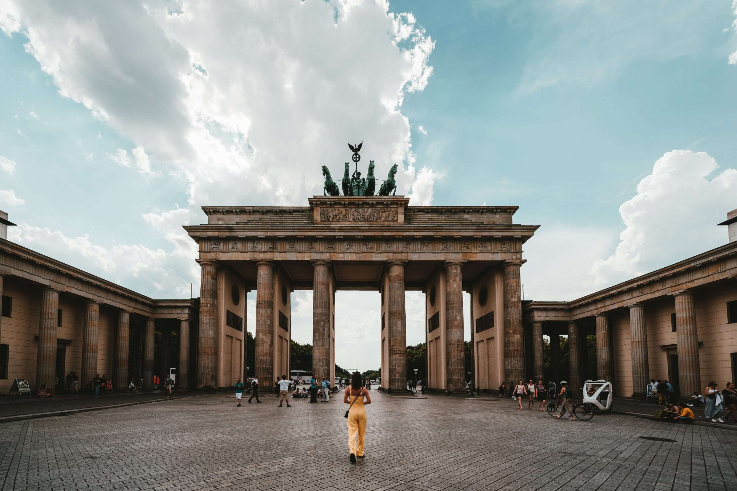 lady wearing yellow walks towards Brandenburg Gate in Berlin, Germany