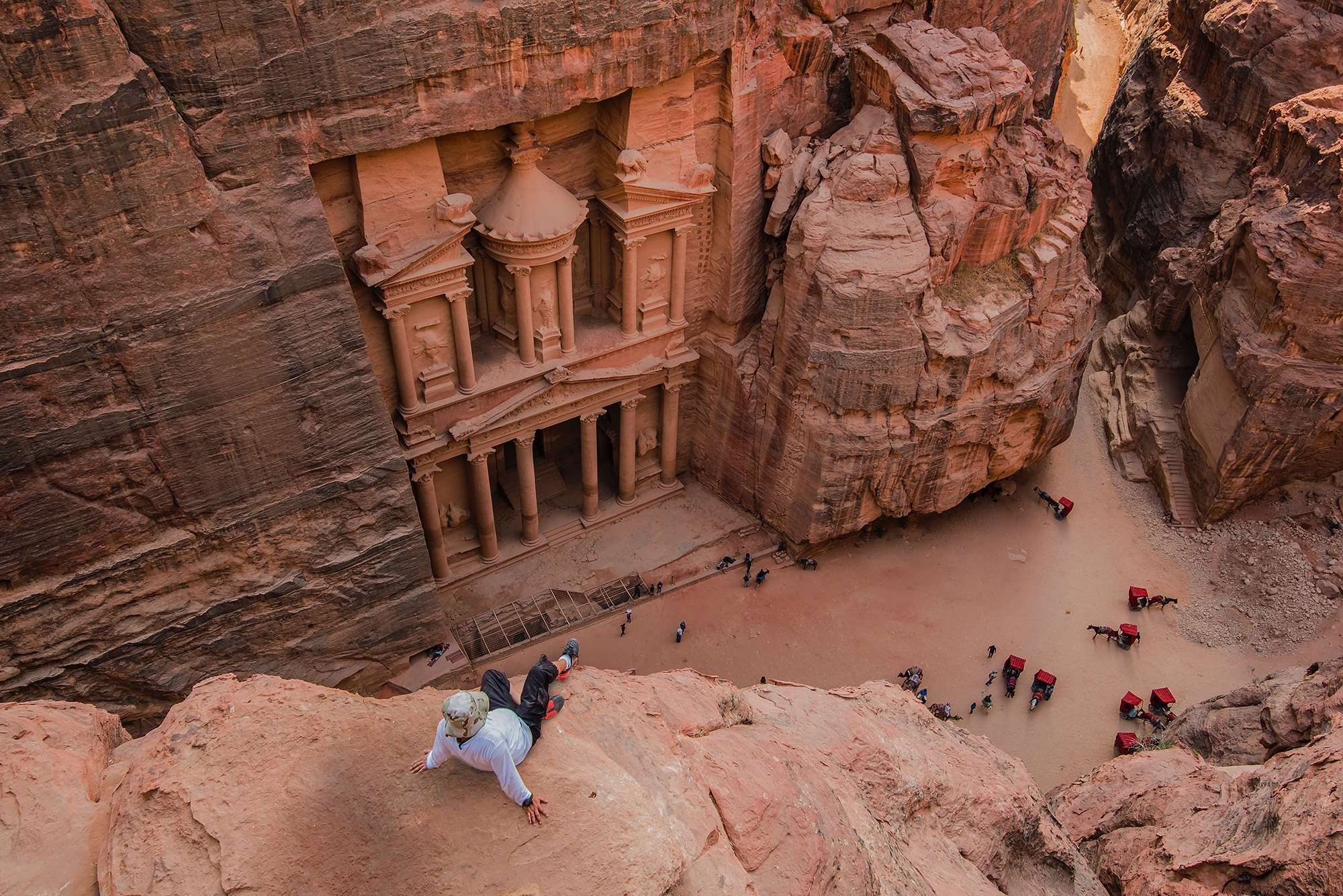 man in a white shirt sits on a rock looking down at a historical site during travel to Petra