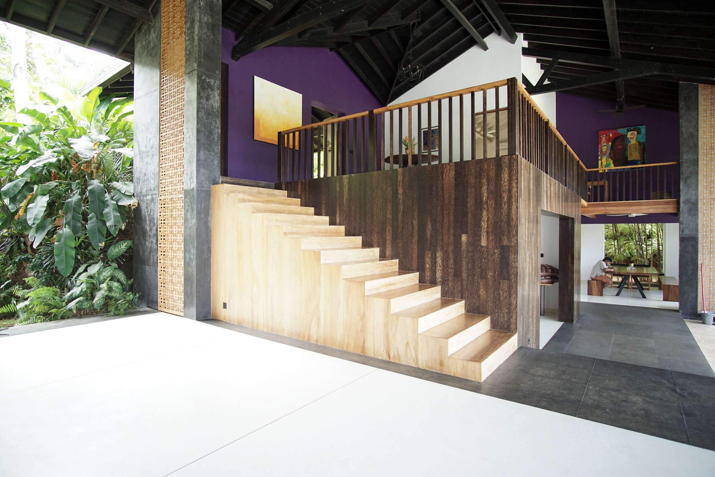 side view of wooden stairs leading up to a purple wall and entrance at Villa Wambatu