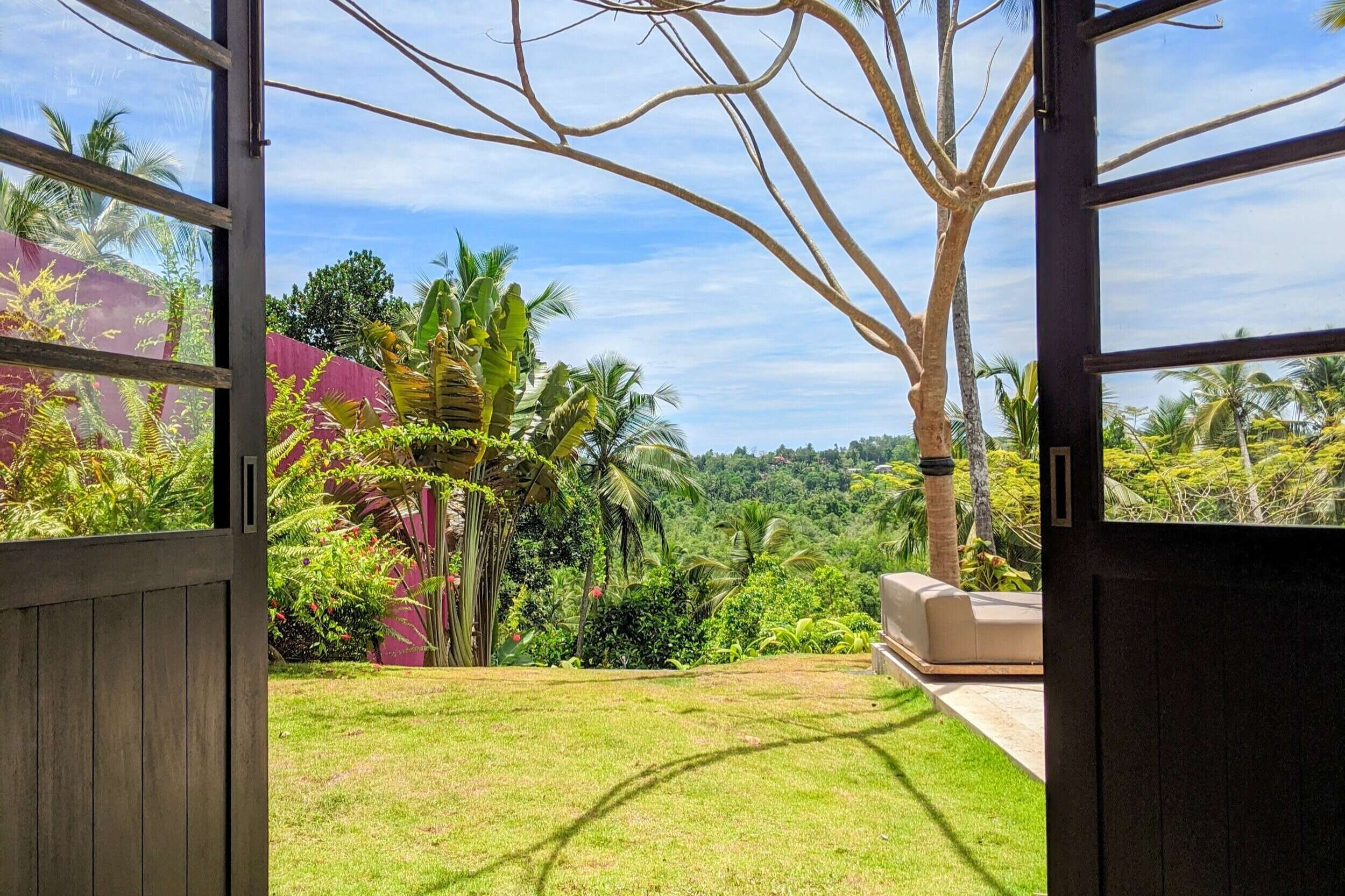 looking out of patio doors at Villa Wambatu, with blue sky, green grass and trees